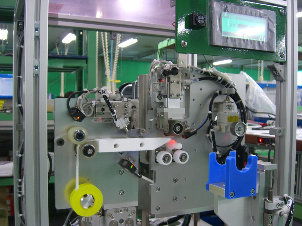 自動化装置によるガスボンベへのシールテープ巻作業の高効率化